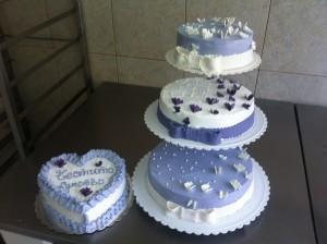 Сватбена торта на три етажа с панделка от захарно тесто и пеперуди и допълнителна торта за кумуване.