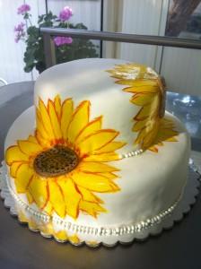 Двуетажна сватбена торта, облечена в захарно тесто с рисувани слънчогледи.